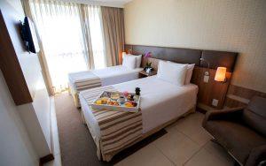 quarto com cama de solteiro do hotel em Brasília Hplus Athos Bulcão